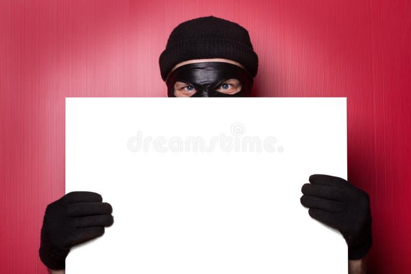 Ladrão que esconde atrás do anúncio imagem de stock royalty free