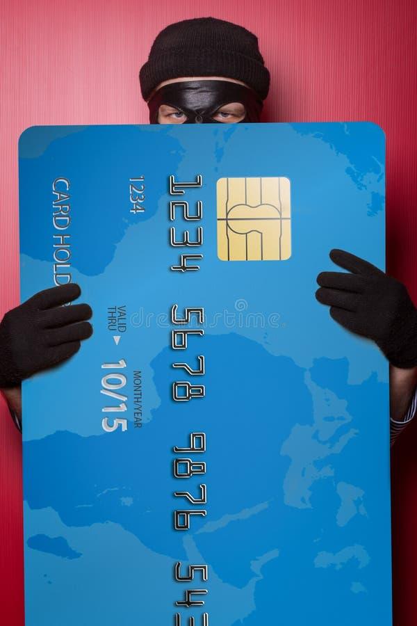 Ladrão que esconde atrás do cartão de crédito azul grande fotos de stock