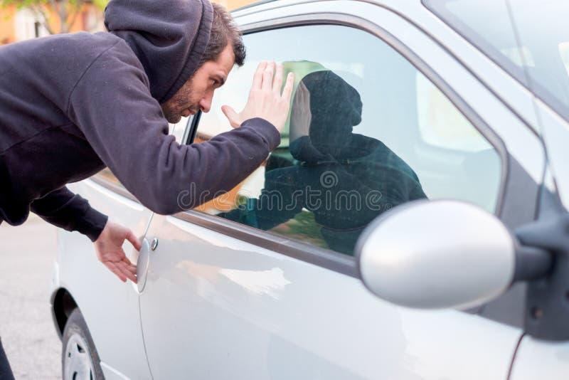 Ladrão que olha dentro de uma janela de carro pronta para roubar foto de stock