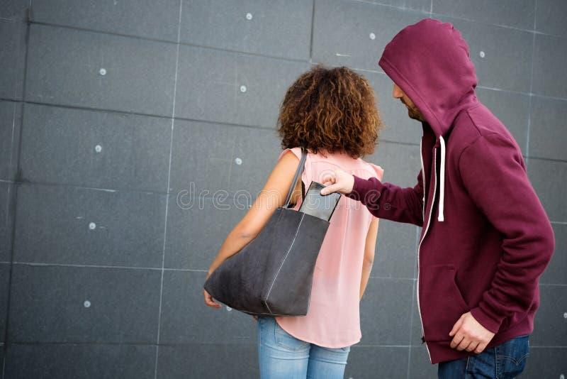 Ladrão que rouba a carteira do saco de uma mulher confundida fotografia de stock royalty free