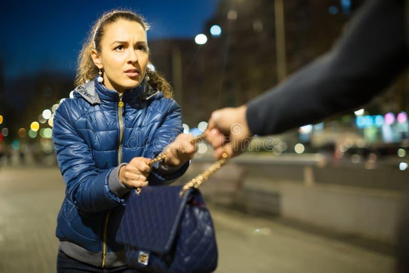 Ladrão que tenta roubar o saco na noite foto de stock