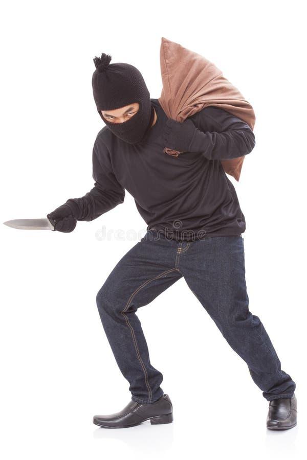 Ladrón con el bolso y el cuchillo el sostenerse foto de archivo