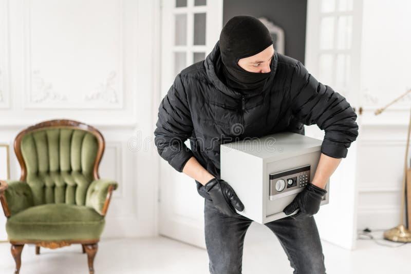 Ladrón con el pasamontañas negro que roba la caja segura electrónica moderna El ladrón confía un crimen en el apartamento de lujo fotografía de archivo libre de regalías