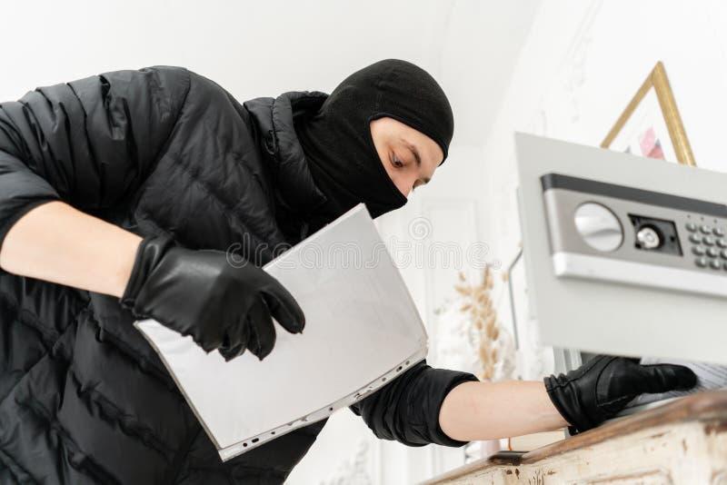 Ladrón con el pasamontañas negro que roba la caja segura electrónica moderna El ladrón confía un crimen en el apartamento de lujo imagen de archivo libre de regalías