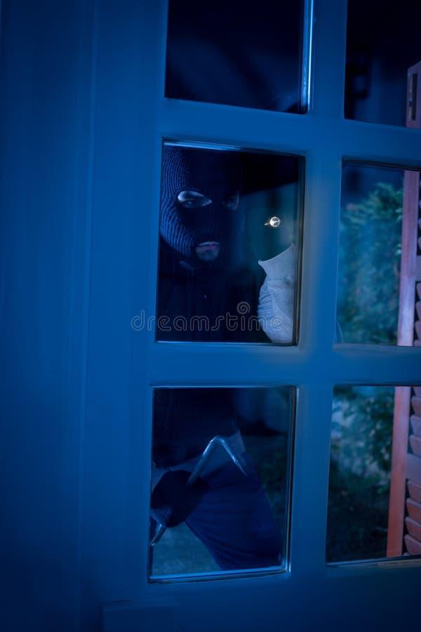 Ladrón con la palanca que se rompe en una casa imagen de archivo libre de regalías