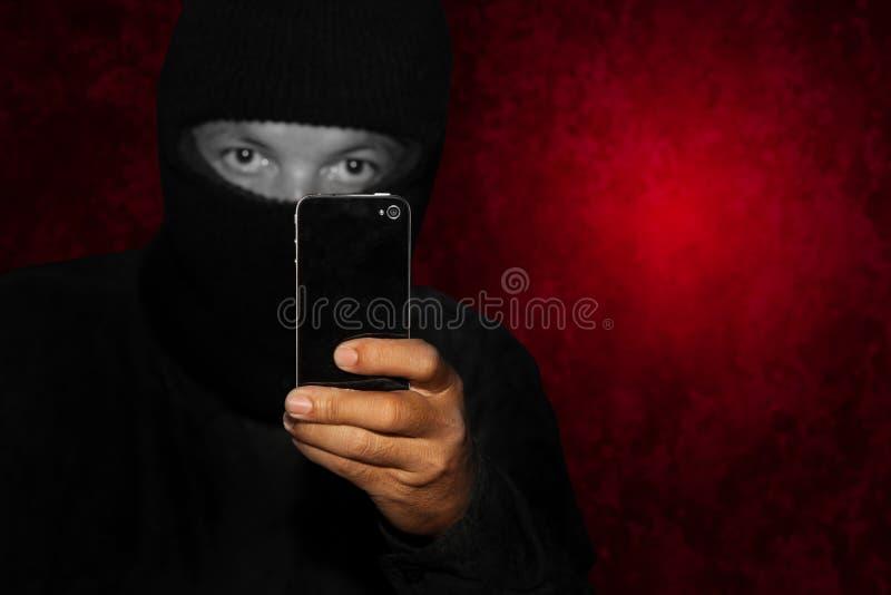 Ladrón con smartphone fotografía de archivo libre de regalías
