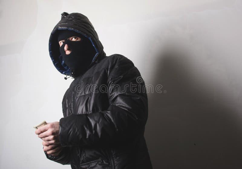 Ladrón con un arma aming imagenes de archivo