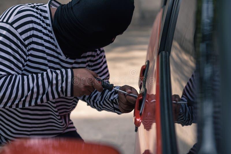 Ladrón de coches que intenta desbloquear un coche por el destornillador fotos de archivo libres de regalías