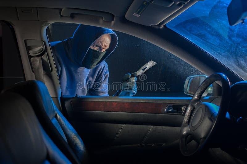Ladrón de coches que mira para abrir un vehículo bloqueado fotografía de archivo