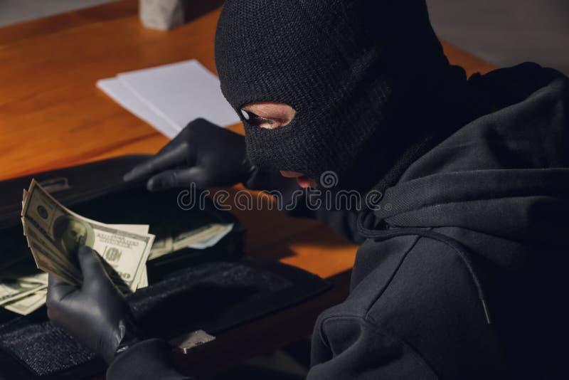 Ladrón de sexo masculino que roba la cartera con el dinero en oficina fotografía de archivo libre de regalías