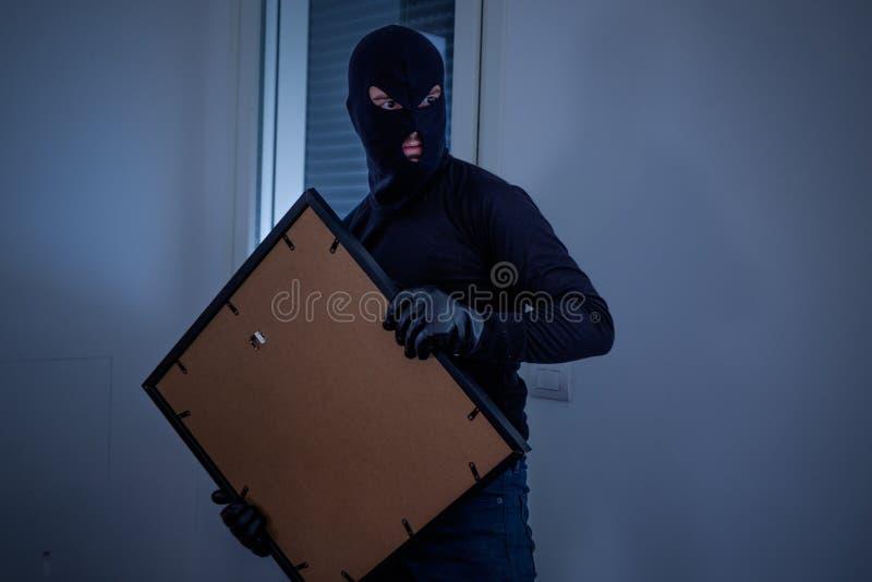 Ladrón dentro del hogar que roba una pintura imagen de archivo