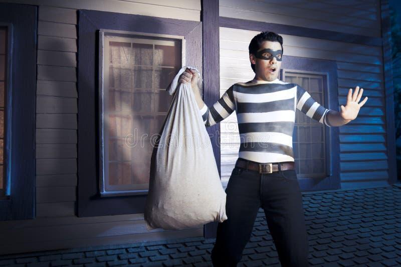 Ladrón en la azotea de una casa en la noche foto de archivo