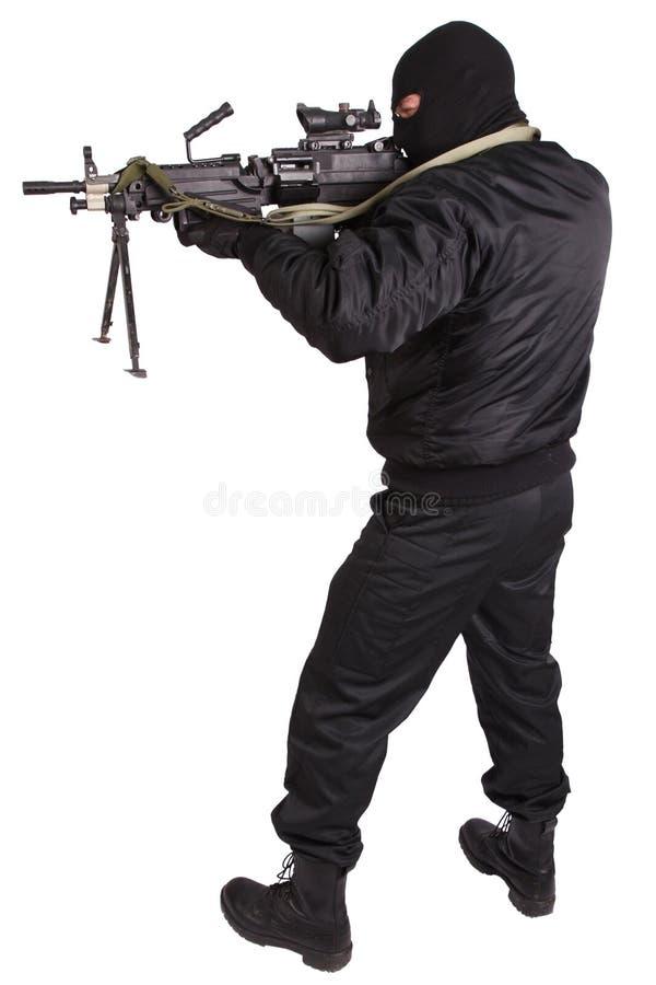 Ladrón en uniforme del negro y máscara con la ametralladora foto de archivo libre de regalías