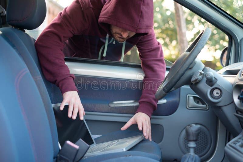 Ladrón encapuchado que roba un ordenador portátil del ordenador de un coche parqueado imagen de archivo