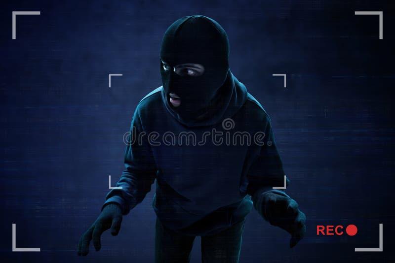 Ladrón enmascarado cogido en la cámara de seguridad fotografía de archivo