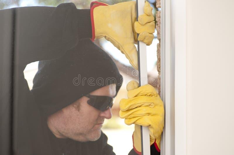 Ladrón que se rompe a través de la ventana de la casa imagen de archivo