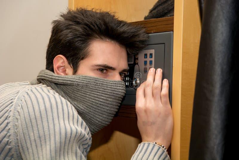 Ladrón masculino joven que abre una pequeña cámara acorazada casera o imágenes de archivo libres de regalías