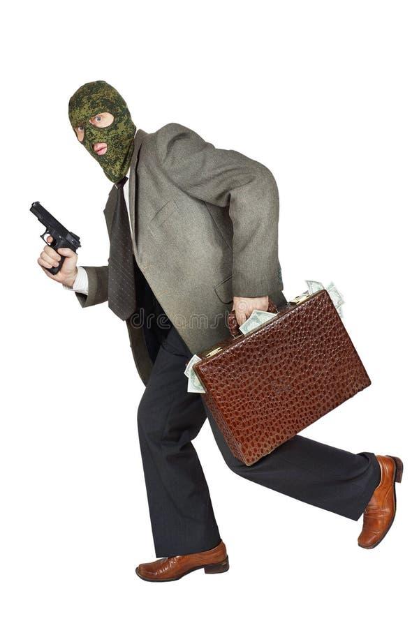 Ladrón que corre con el arma y una cartera por completo de dinero foto de archivo libre de regalías