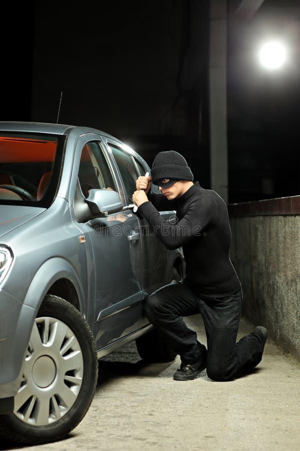 Ladrón que desgasta una máscara del robo que intenta robar un coche imágenes de archivo libres de regalías
