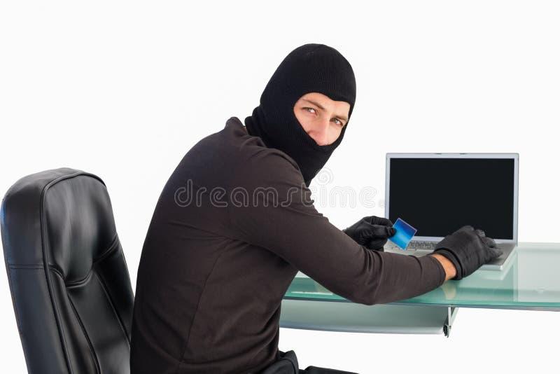 Ladrón que hace compras en línea con el ordenador portátil mientras que mira la cámara imagenes de archivo