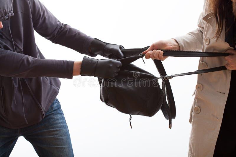Ladrón que intenta arrebatar una mochila imagen de archivo