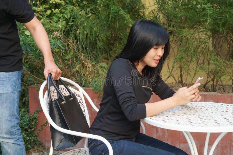 Ladrón que intenta robar y caminar lejos el bolso mientras que mujer foto de archivo libre de regalías