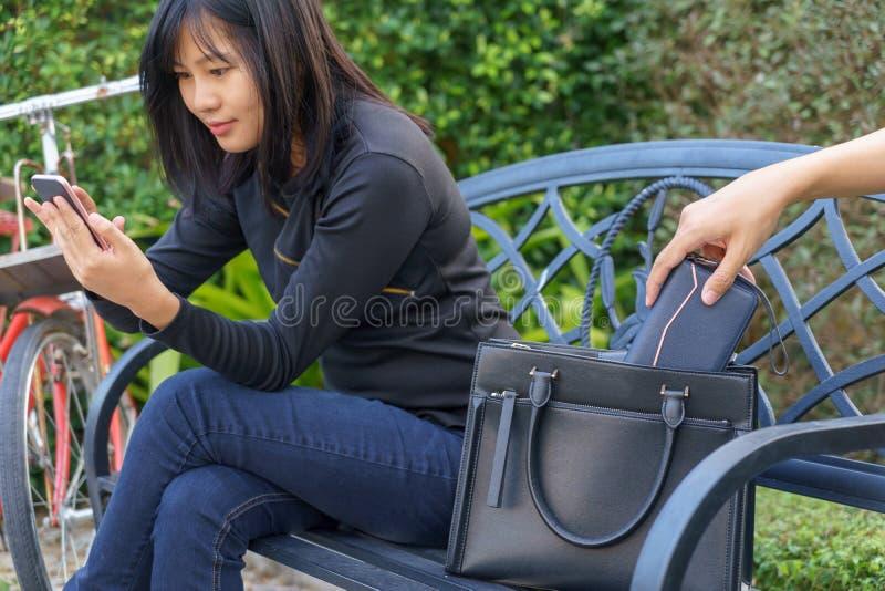 Ladrón que intenta robar y caminar lejos la cartera mientras que el usar de la mujer fotos de archivo