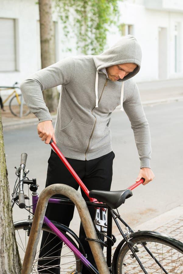 Ladrón que intenta romper la cerradura de la bicicleta imagenes de archivo