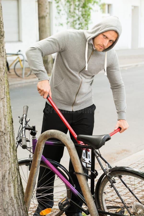 Ladrón que intenta romper la cerradura de la bicicleta fotografía de archivo