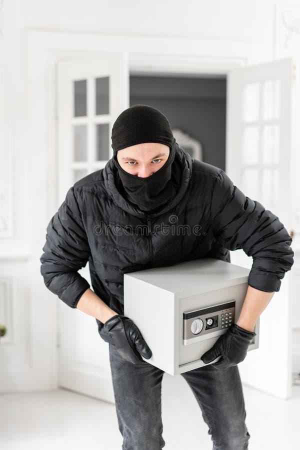 Ladrón que mira la cámara con el pasamontañas negro que roba la caja segura electrónica moderna El ladrón confía un crimen adentr imagen de archivo libre de regalías