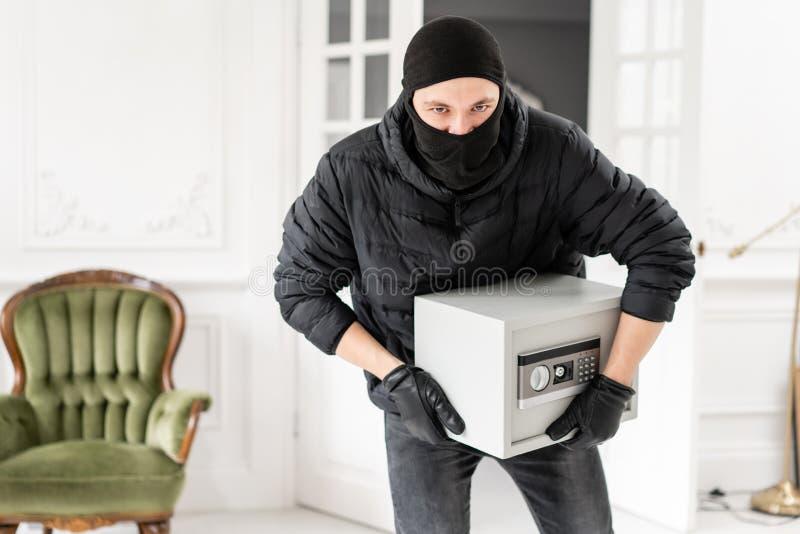 Ladrón que mira la cámara con el pasamontañas negro que roba la caja segura electrónica moderna El ladrón confía un crimen adentr foto de archivo libre de regalías