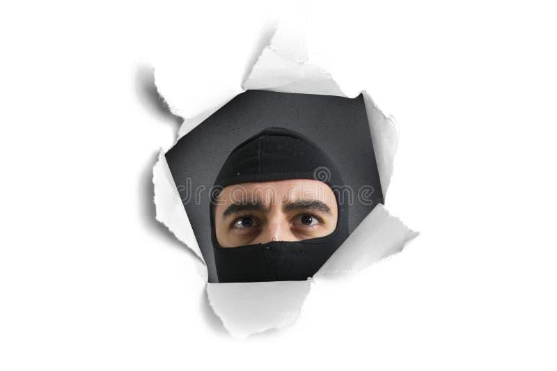 Ladrón que mira a través de un agujero de papel fotos de archivo