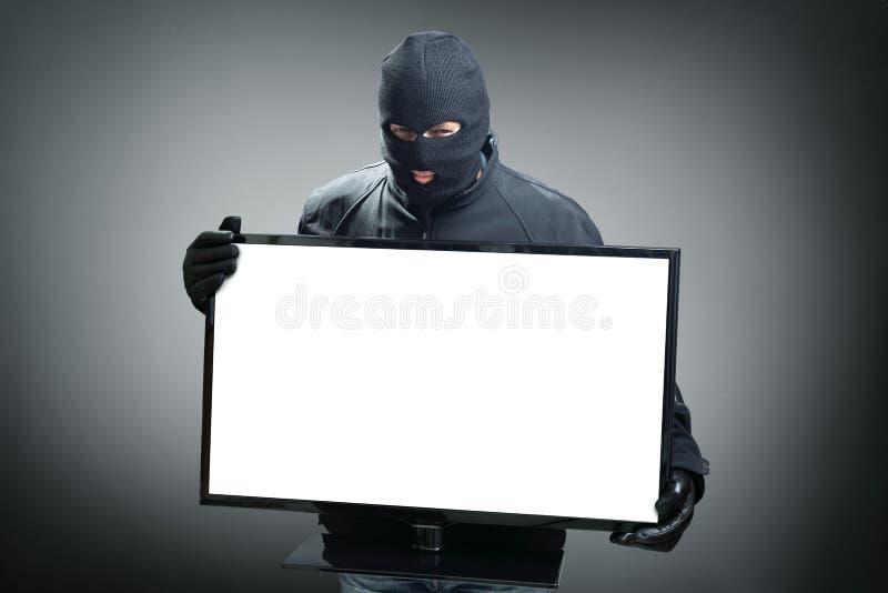 Ladrón que roba el monitor de computadora imagen de archivo