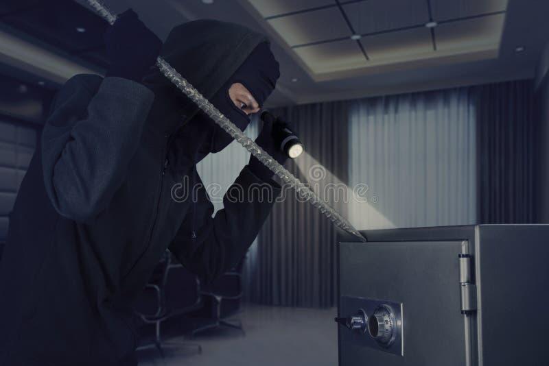 Ladrón que roba una caja de depósito seguro fotografía de archivo