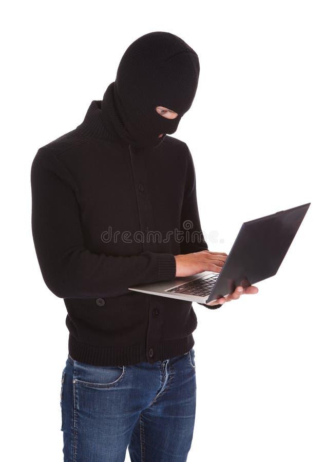 Ladrón que usa el ordenador portátil fotografía de archivo