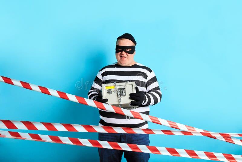 Ladrón regordete gordo alegre que roba el dinero de la caja fuerte foto de archivo libre de regalías