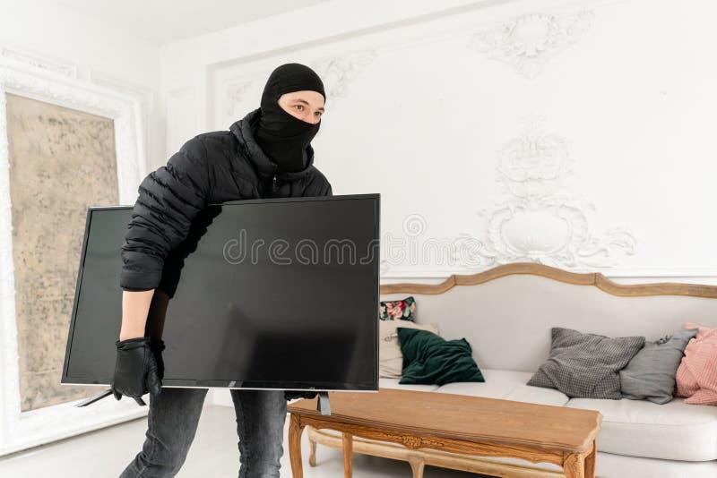 Ladr?n del hombre que roba el aparato de TV de la casa Ladr?n con el pasamonta?as negro que roba la televisi?n costosa moderna lu imagen de archivo