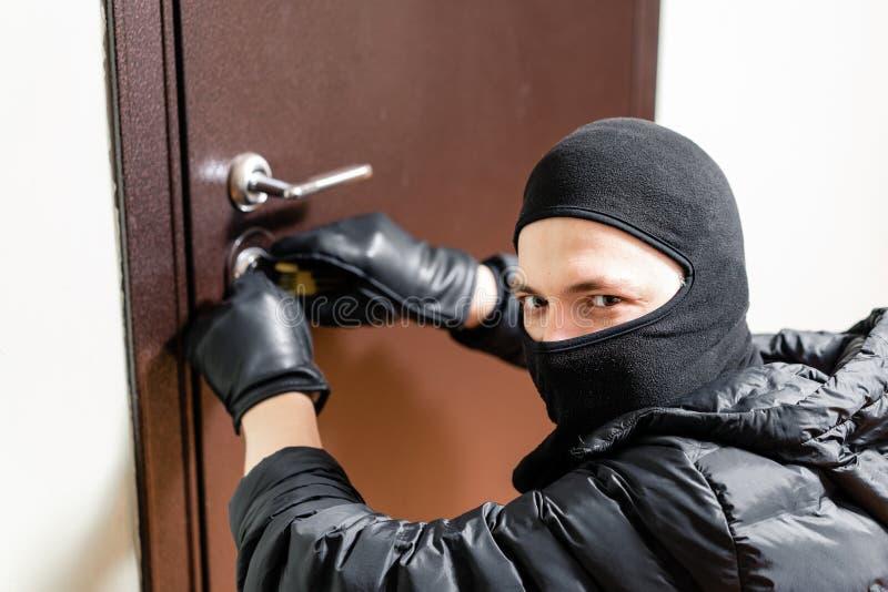 Ladr?n enmascarado que usa al recogedor de la cerradura a la puerta bloqueada abierta imagen de archivo libre de regalías
