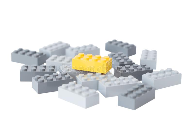 Ladrillo amarillo del juguete encima de ladrillos grises imagen de archivo libre de regalías