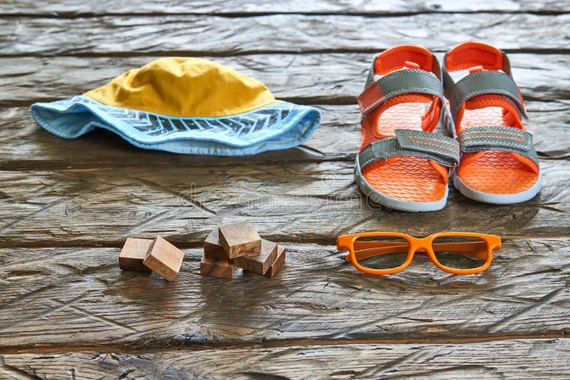 Ladrillos de madera, sombrero, sandalia, gafas de sol imagen de archivo