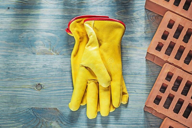 Ladrillos rojos de los guantes protectores en concep de la construcción del tablero de madera fotografía de archivo