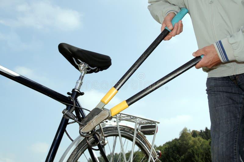 Ladro che braeking fuori da una serratura della bicicletta con uno strumento immagini stock