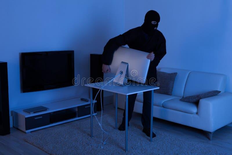 Ladro che ruba il monitor del computer dal salone immagine stock libera da diritti