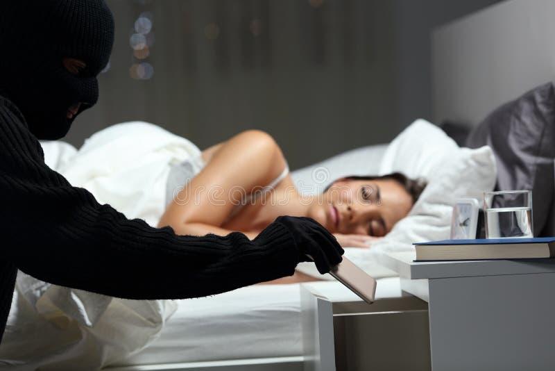 Ladro che ruba un telefono in una camera da letto immagini stock