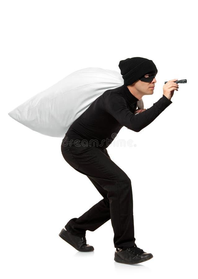 Ladro che trasporta un sacchetto e che tiene una torcia fotografia stock