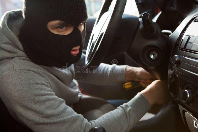 Ladro che utilizza cacciavite nell'automobile fotografia stock libera da diritti