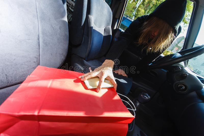 Ladro dello scassinatore che ruba smartphone e borsa dall'automobile fotografie stock