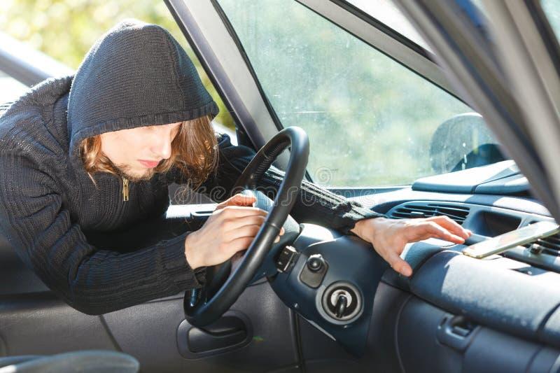 Ladro dello scassinatore che si rompe nello smartphone rubare di automobile immagine stock libera da diritti
