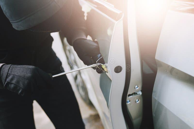 Ladro di automobile un uomo in vestiti neri superiori incappucciati e guanti di usura che si rompono in una porta di automobile c fotografia stock