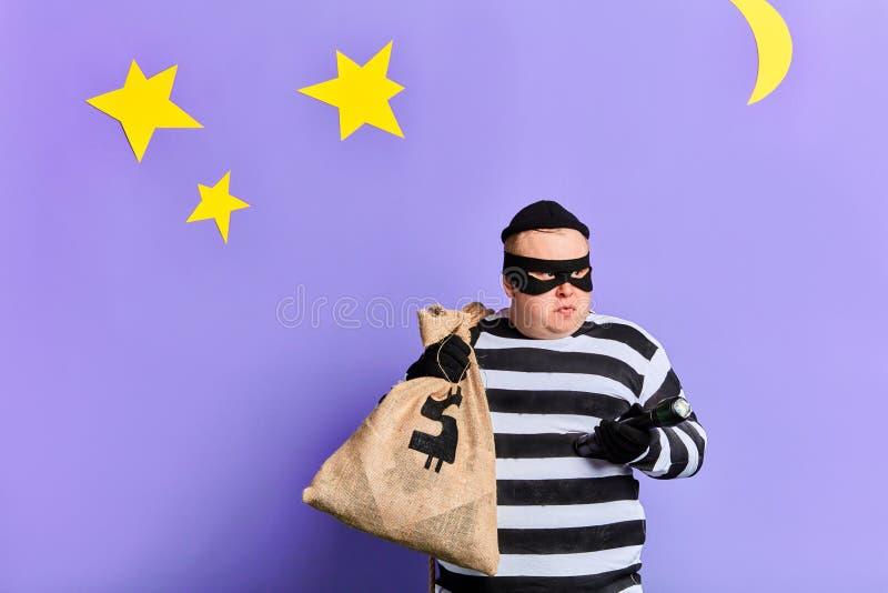Ladro grasso serio che porta una grande borsa, vestita in vestiti a strisce, maschera fotografie stock libere da diritti